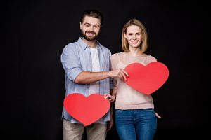 Couple holding red paper hearts