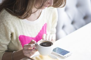 Fashionable girl in yellow blouse sitting in a cafe and drink coffee while viewing the message on the phone.