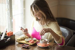 Young business woman eating sushi for lunch at a small café and a healthy lifestyle, working on a smartphone. Happy smiling, fashionable, in a yellow sweater.