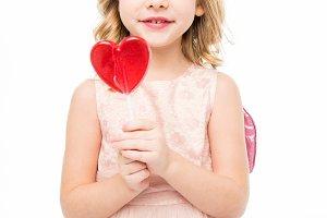 Girl holding heart shaped lollipop