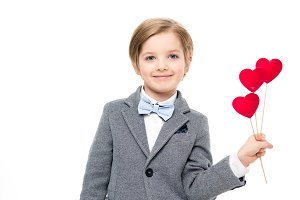 Little boy holding paper hearts