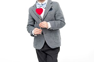 Little boy with paper heart on stick