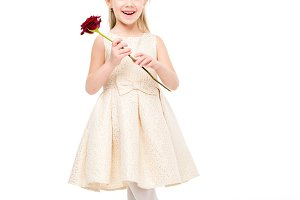 Little girl holding red rose