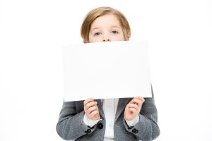 Boy hiding face behind blank card