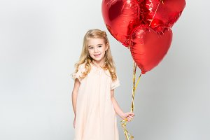 Little girl with bundle of balloons