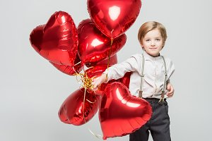 Boy with bundle of heart balloons