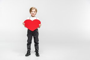 Boy holding big red paper heart