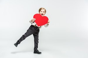 Happy boy with red paper heart