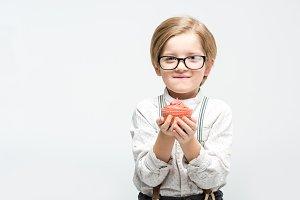 Little boy holding cupcake