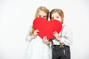 Kids hiding faces behind red heart