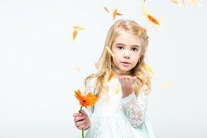 Girl blowing petals of flower
