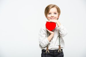 Boy holding red heart sign
