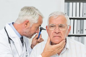 Close-up of a male doctor examining senior patients ear