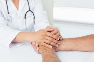Close-up mid section of a doctor holding patients hands