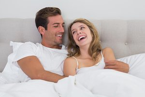 Cheerful relaxed couple sitting in bed