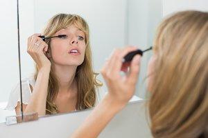 Close-up of a beautiful woman applying mascara