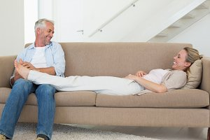 Caring man giving his partner a foot rub on the couch