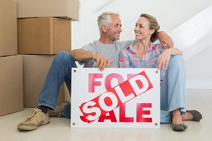 Happy couple sitting on floor with sold sign