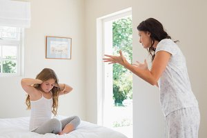 Girl covering ears while mother scolding bedroom