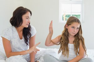 Girl showing stop gesture to angry mother in bed