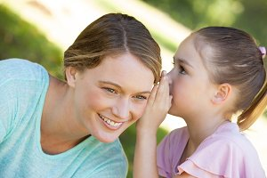 Girl whispering secret into mothers ear at park