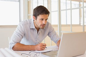 Businessman working on blueprints and laptop in office