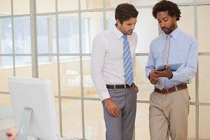 Businessmen using digital tablet in office