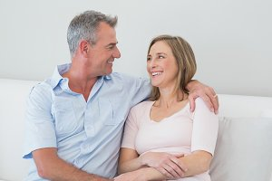 Relaxed couple sitting on sofa with arm around