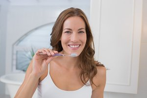 Portrait of a smiling woman brushing teeth