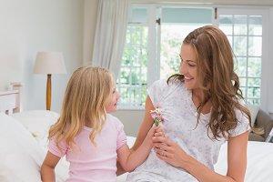 Little girl giving flower to her mother in bedroom