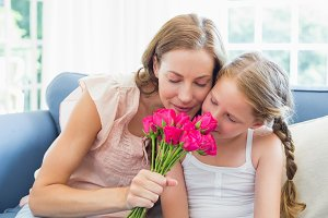 Mother and daughter smelling flowers in the living room