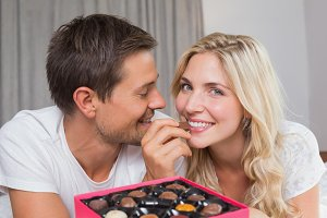 Relaxed happy couple eating candies