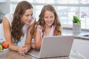 Girl and mother using laptop in house