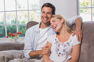 Relaxed loving young couple sitting on sofa