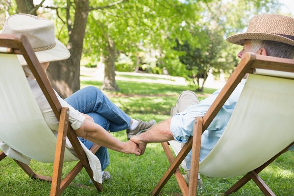 Mature couple sitting in deck chair…