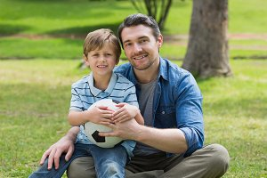 Portrait of father and son with ball at park
