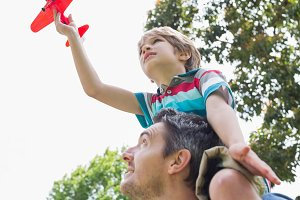 Boy with toy aeroplane sitting on fathers shoulders