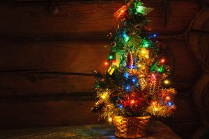 Small Christmas tree with multi colored lights at dark countryside room