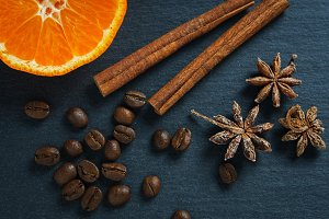Ingredients: anise star, cinnamon sticks, coffee beans and tangerine. Top view