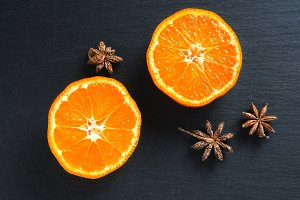 Top flat view: tangerine half and anise stars on black slate stone surface
