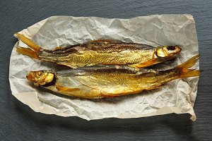 Golden smoked fish on paper and black slate stone