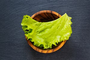 Fresh green lettuce leaf in wooden bowl on black slate stone  as template food background. Top flat view