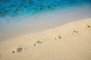 Diagonal footprints on sand beach with sea edge line
