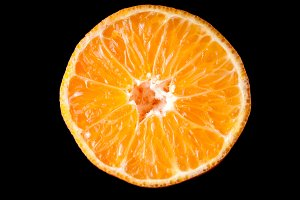 Orange tangerine fruit half slice isolated on black background