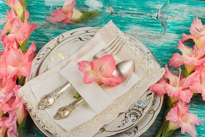 Tableware and silverware with light pink gladiolus