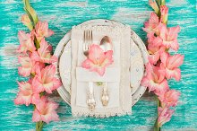 Tableware and silverware with light pink gladiolus containing gladiolus