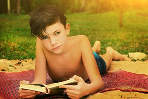 teen boy reading book on the beach