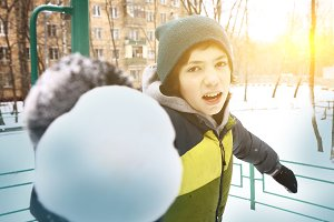 teen boy make snow ball on winter outdoors