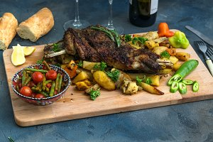 Roast shoulder of lamb on baked potato and carrots, wooden board, top view