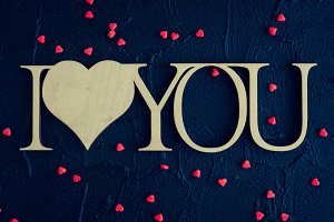 I Love You - wooden phrase on black stone background